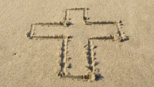 cross drawn in sand