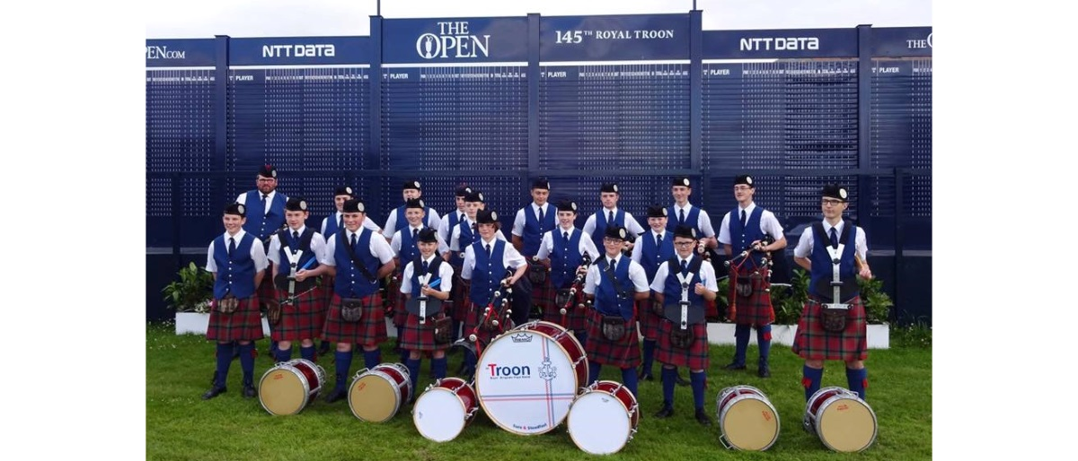 1st Troon BB Pipe Band at the scoreboard of the 145th Open Championship at Royal Troon